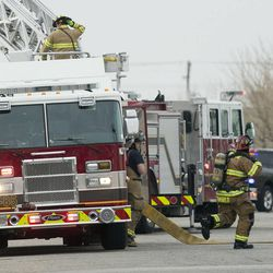 Rescue personnel from multiple agencies work at the crash site of a helicopter that crashed into a building near Sky Park Airport in North Salt Lake Tuesday Dec. 2, 2014.