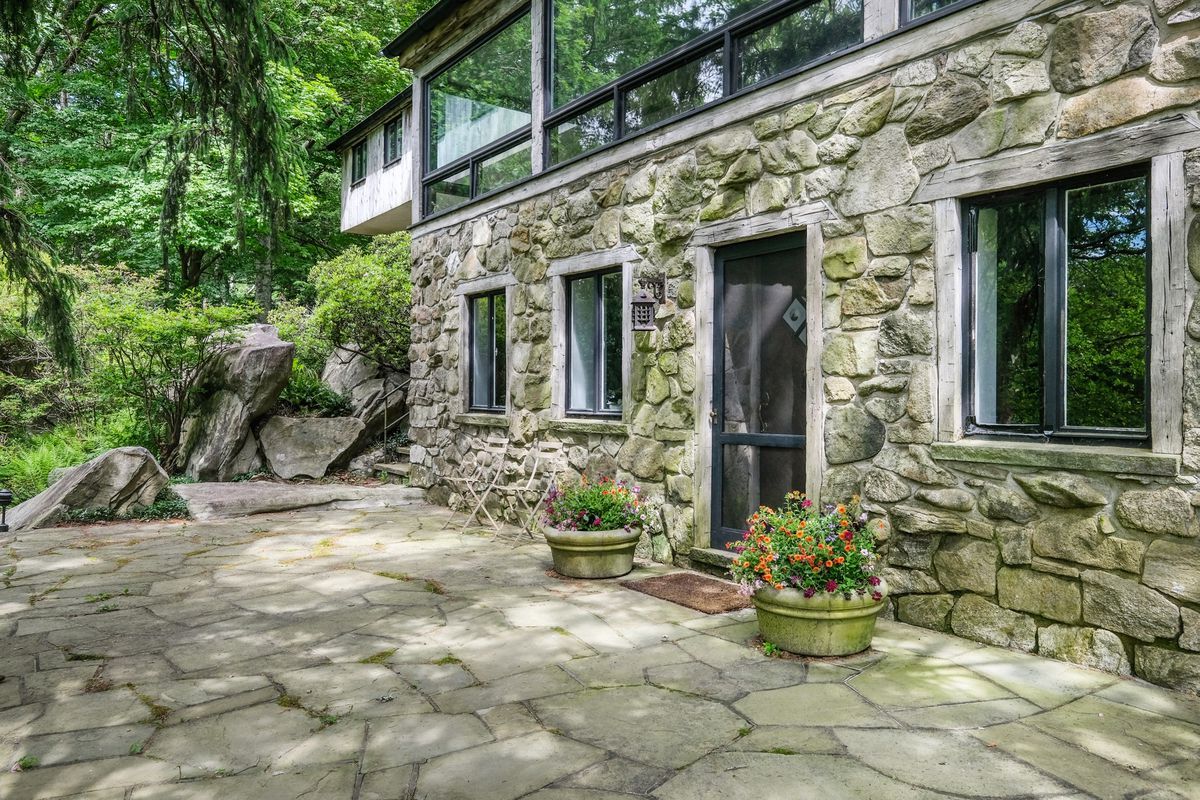 The exterior of a stone house with a second-story of windows. There is a flagstone patio in front of the house.