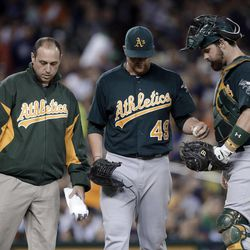 Oakland Athletics starting pitcher Brett Anderson (49) hands catcher Derek Norris the ball as he leaves the baseball game against the Detroit Tigers with trainer Nick Paparesta, left, during the third inning Wednesday, Sept. 19, 2012, in Detroit.