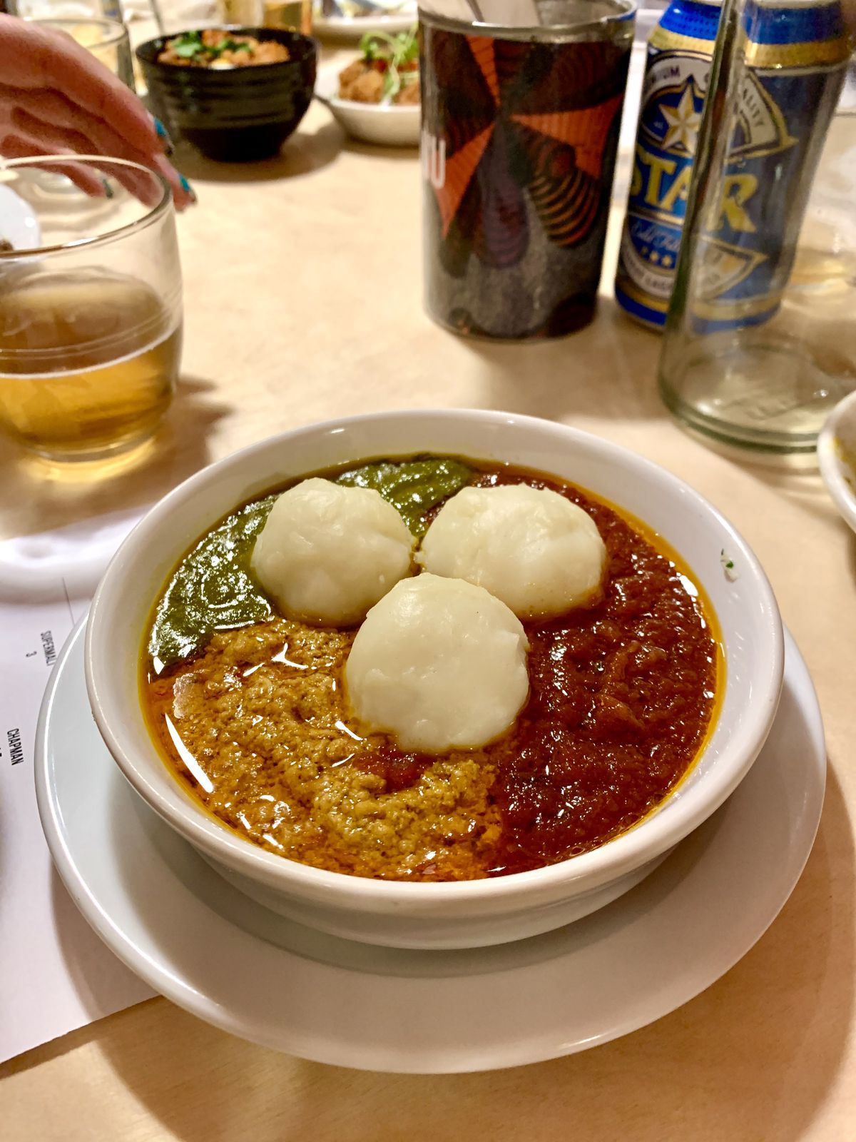 Fufu and egusi in a bowl on a brightly lit table