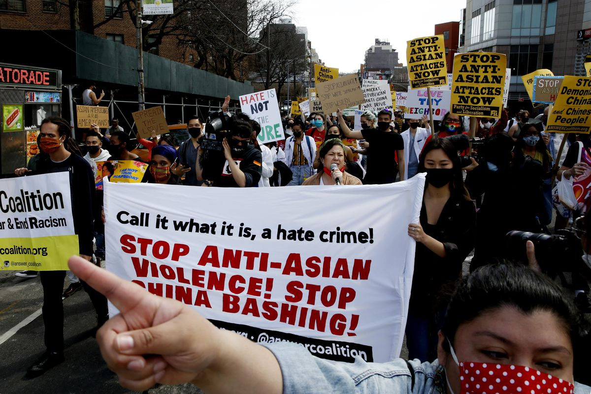 """A crowd of people protest against Anti-Asian violence in New York City. A woman points in front of a banner that reads, """"Call it what it is, a hate crime! Stop Anti-Asian Violence! Stop China Bashing!"""""""