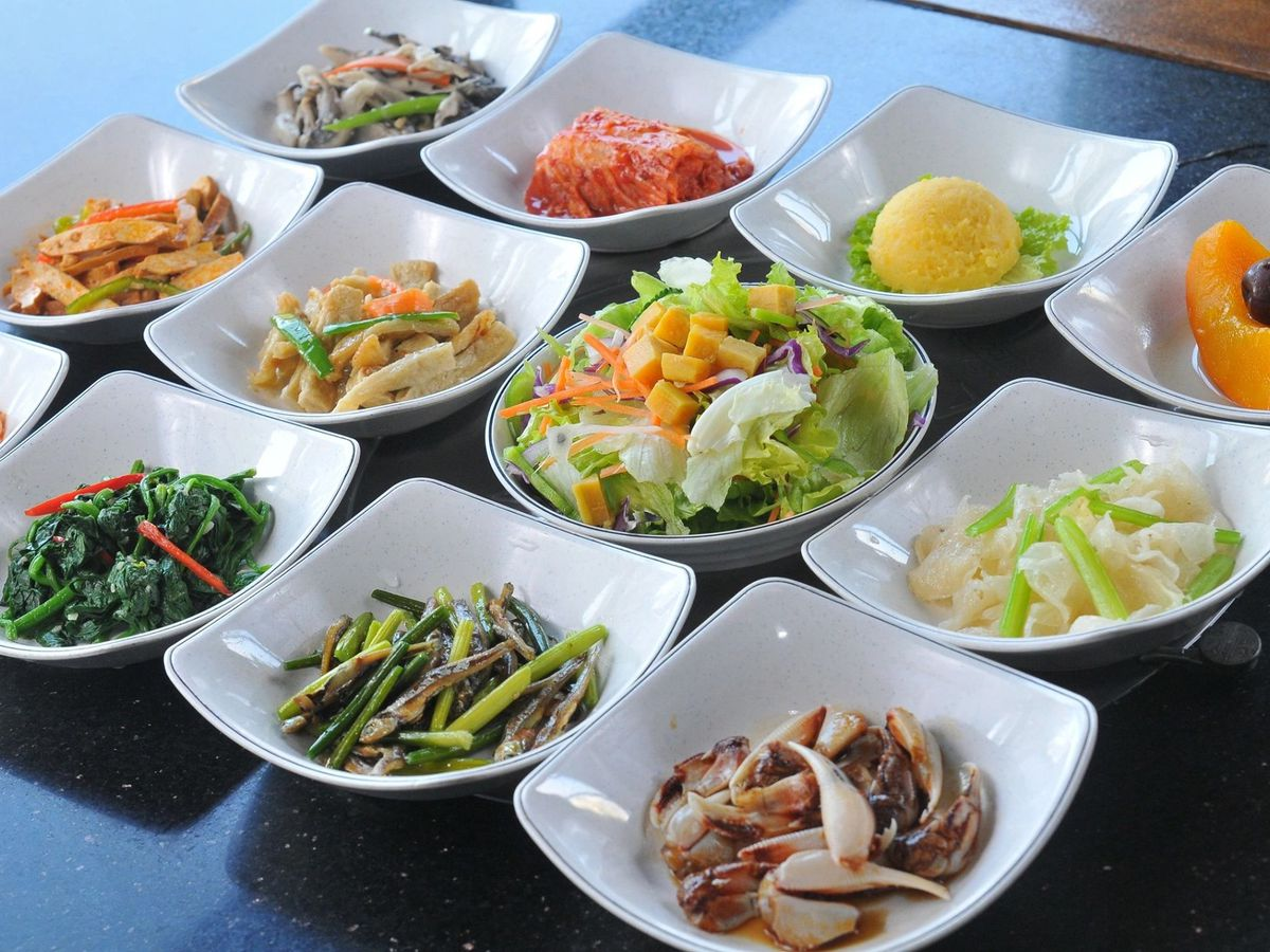 lots of banchan (or side dishes) in small white bowls