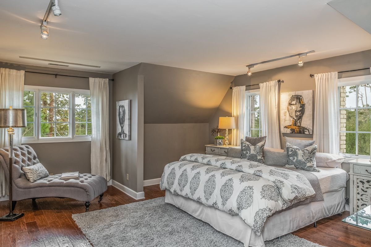 A gray-walled bedroom has windows, a gray rug, and a white and gray comforter.