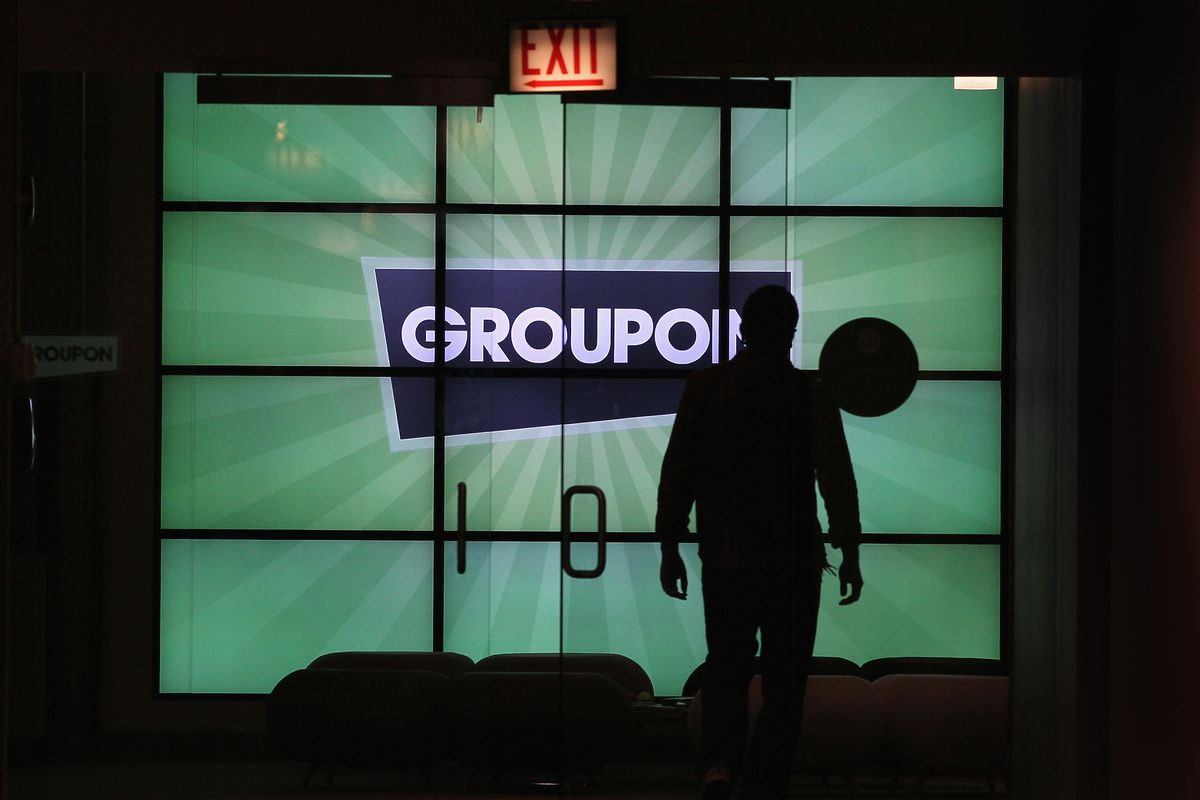 A man silhouetted against a lit glass door and a Groupon sign