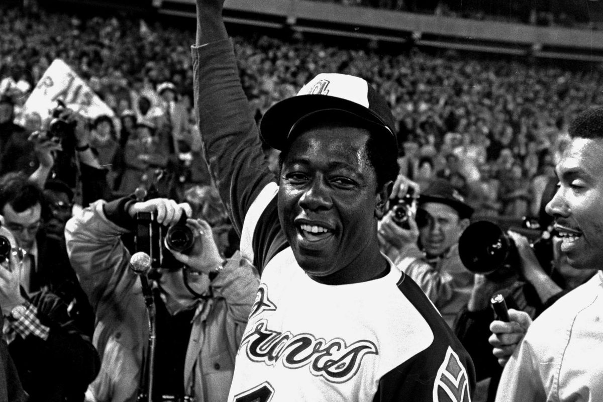 Hank Aaron holds aloft the ball he hit for his 715th career home run against the Dodgers on April 8, 1974.