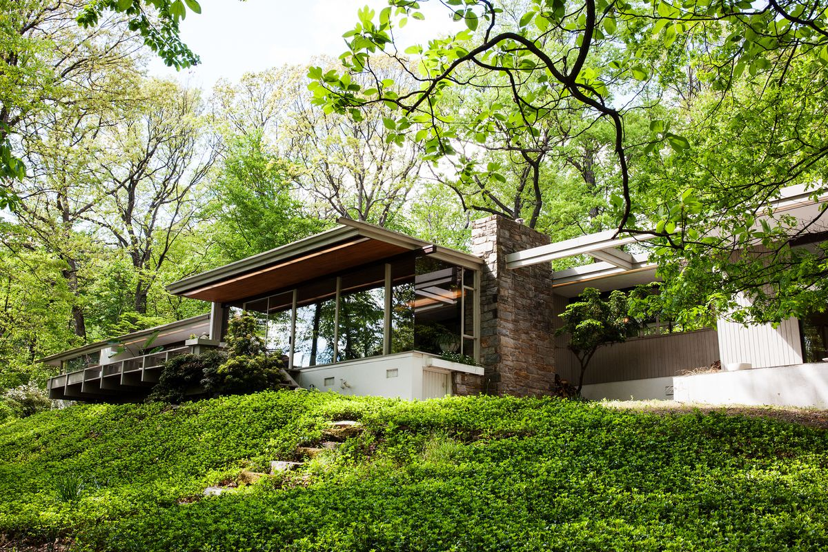 The house is nestled in green, with an ivy lawn and green trees all around.