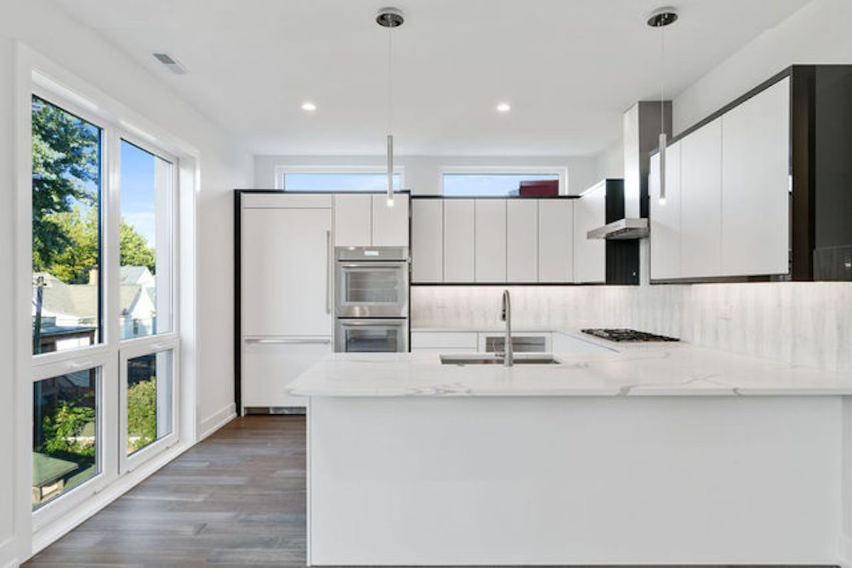 A contemporary kitchen with marble counters and white cabinet doors set against darker casing.