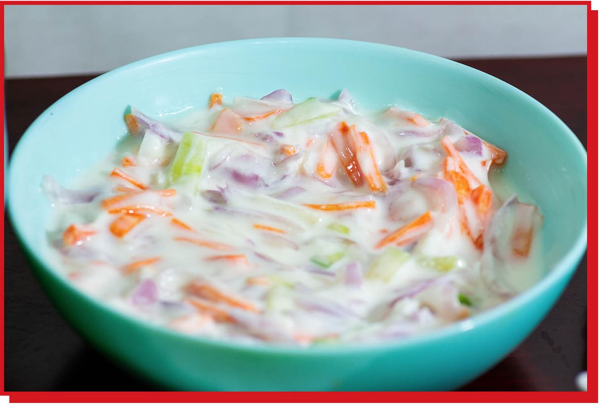 A bowl of shredded carrots, celery, and onions mixed in yogurt.