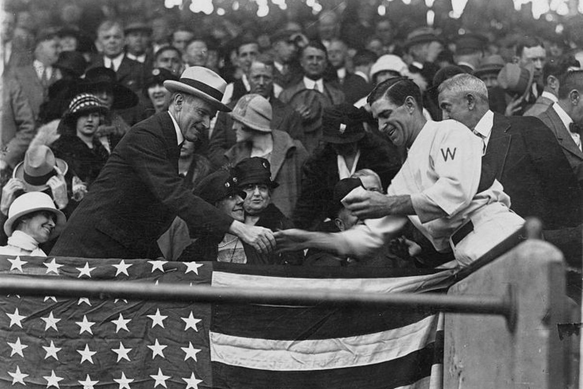 Washington Senators manager Stanley Harris, in the grandstand, presents President Calvin Coolidge (at left) with the baseball used to open the 1924 World Series.