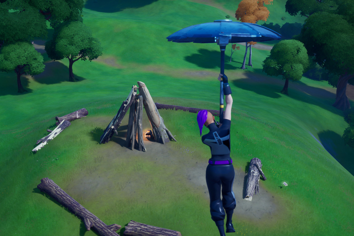 A Fortnite player glides down in front of a Timber Tent