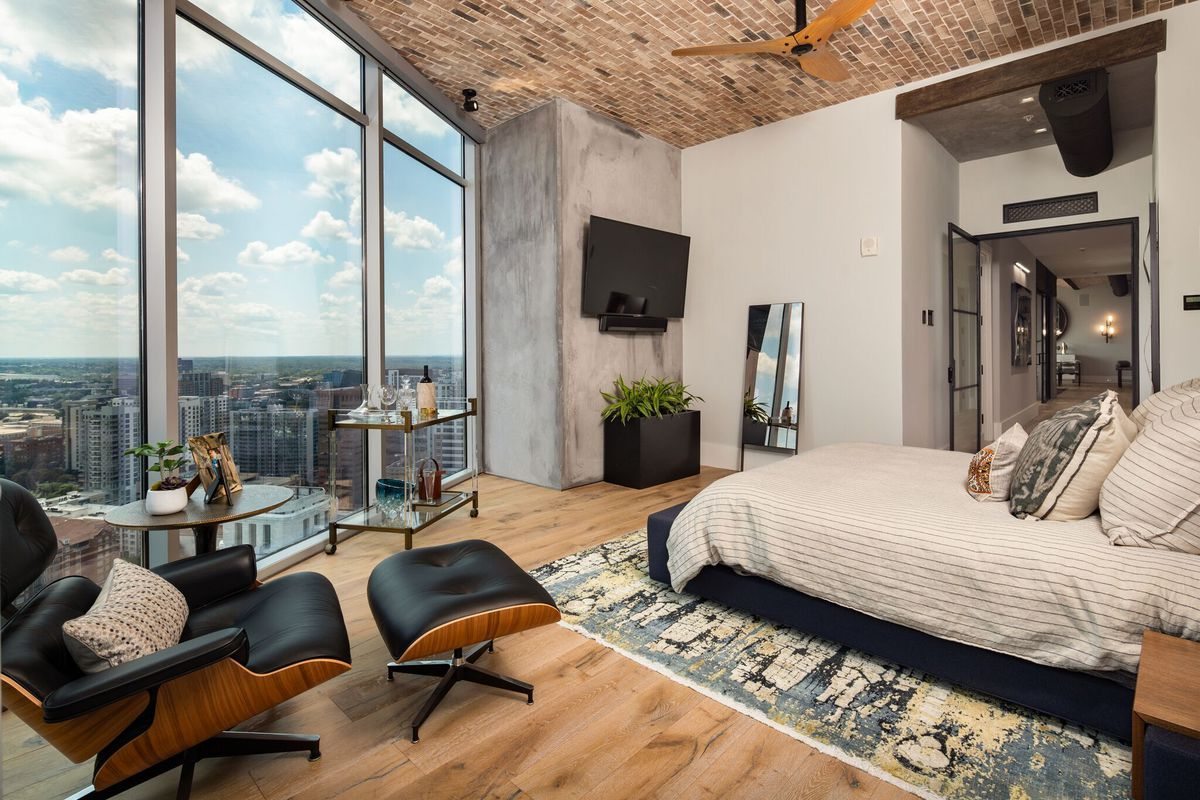 An owner's master bedroom with view across Atlanta and brick ceilings.