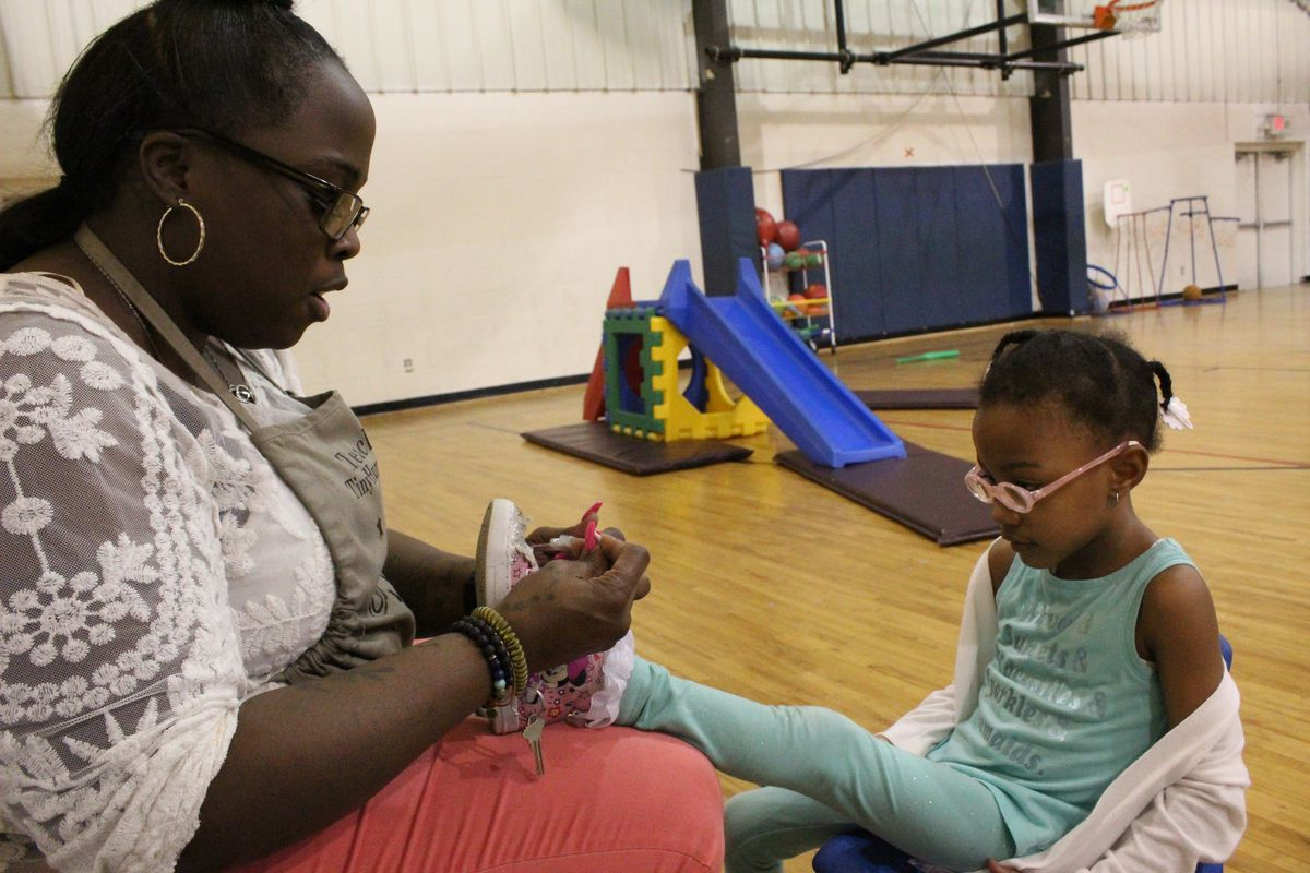 Cindy Lester, ties a shoelace during gym class at Children of the Rising Sun Empowerment Center in northwest Detroit.
