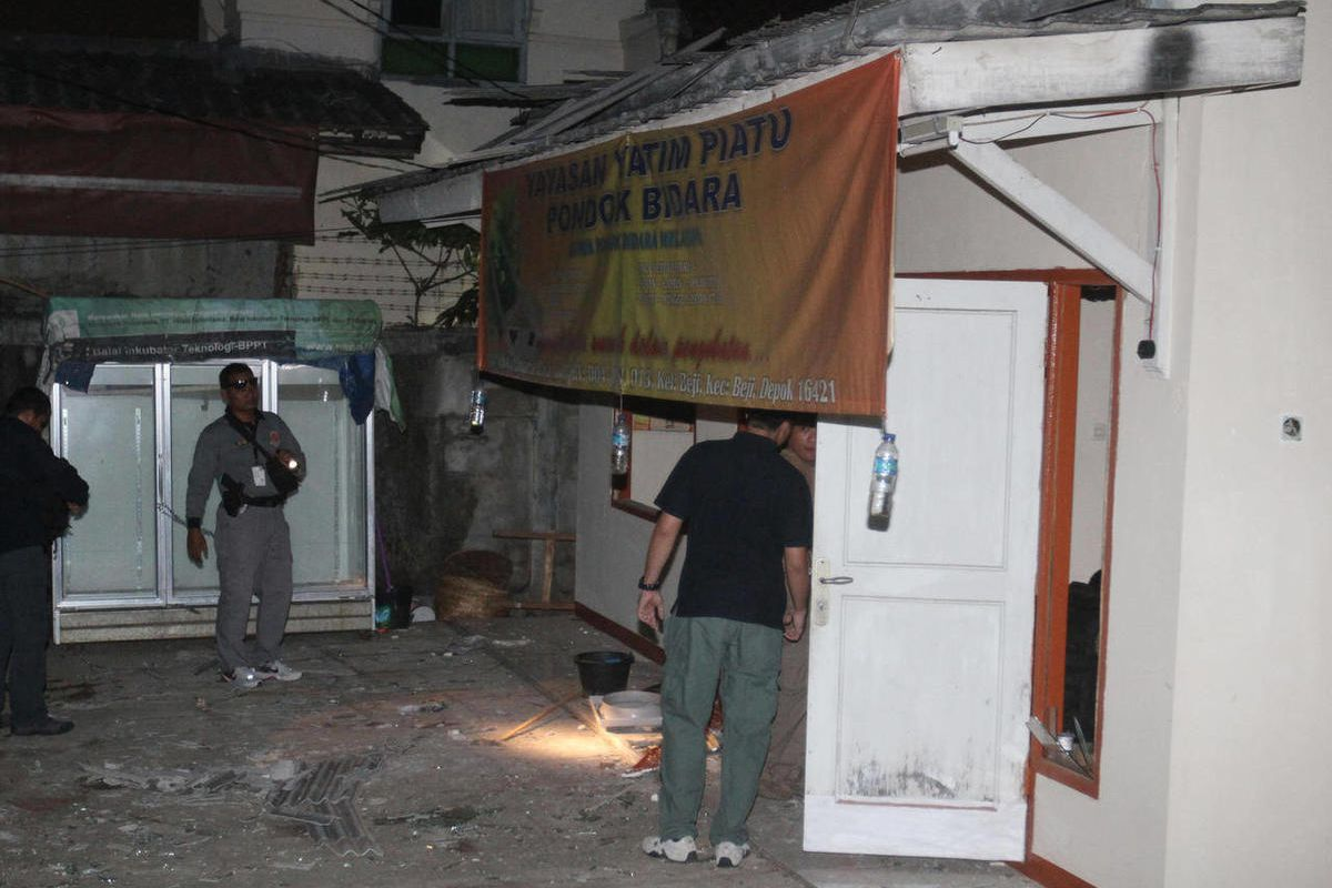 In this late Saturday, Sept. 8, 2012 photo, plain-clothed police officers examine a house where an explosion went off in Depok, West Java, Indonesia. A bomb being prepared for a terrorist attack has exploded at the house injuring five people, police said.