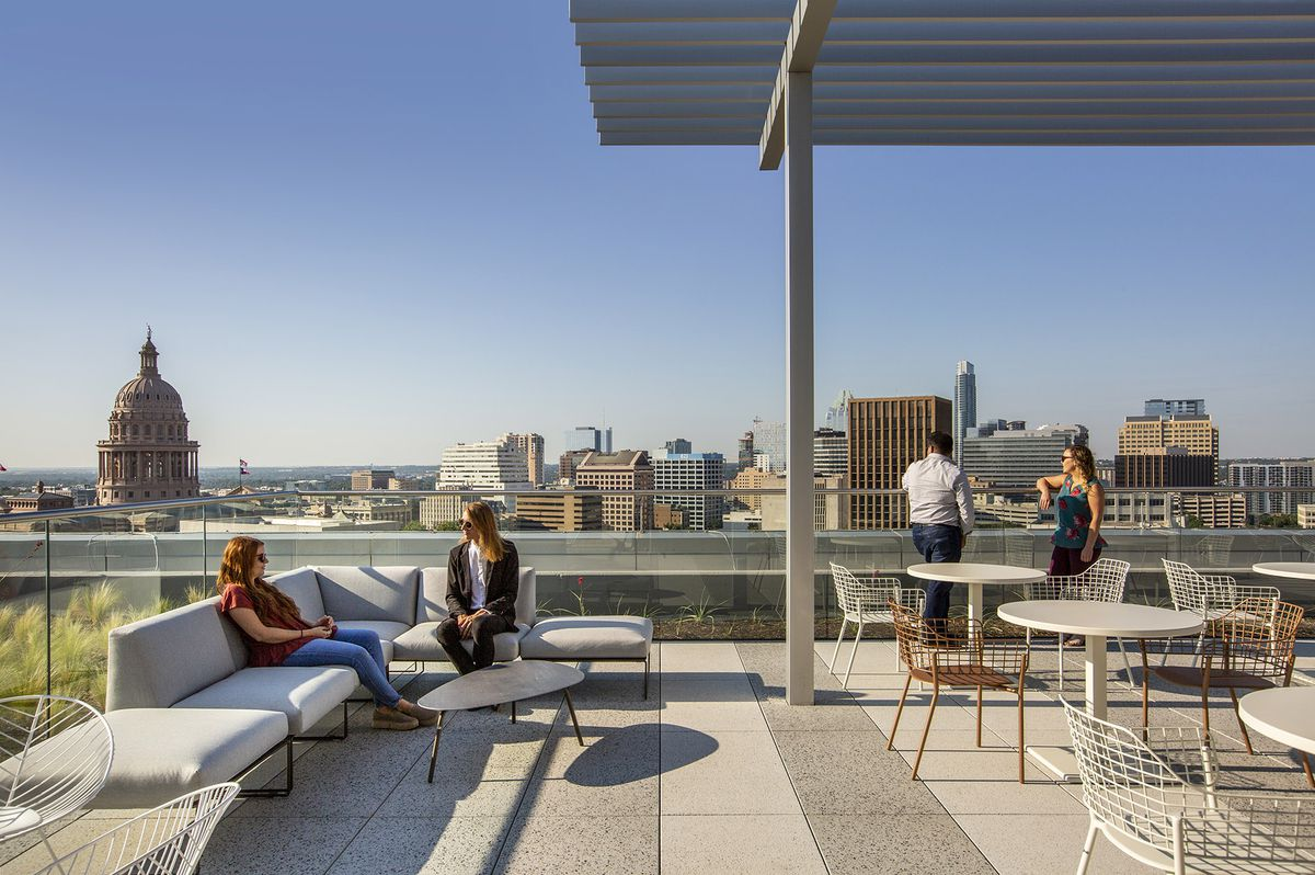 Large rooftop patio with steel pergola, alternating gray and white granite floor, people on couches and at glass railing overlooking Austin skyline toward south, state capitol dome on left