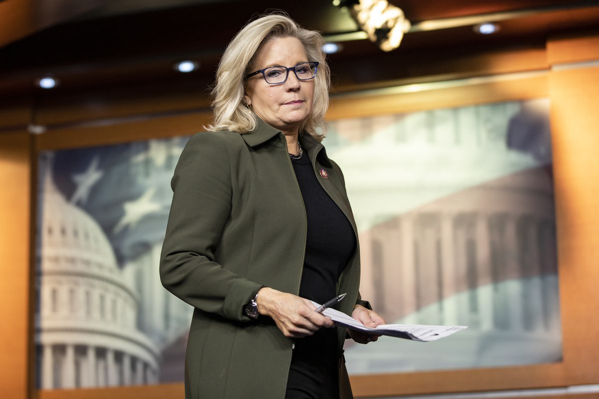 Cheney, in black-rimmed glasses, a dark blouse, and an olive jacket, casts a serious glance at the camera, a stack of papers in her hands.