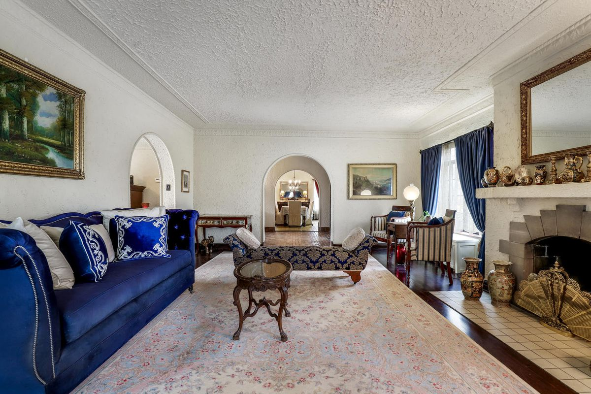 A living room with a blue velvet couch across from a stucco fireplace. There's a pink floral carpet and other sitting furniture.