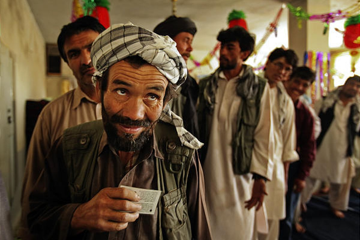 Men wait in line to cast their ballots  at a polling station in Kabul Thursday.