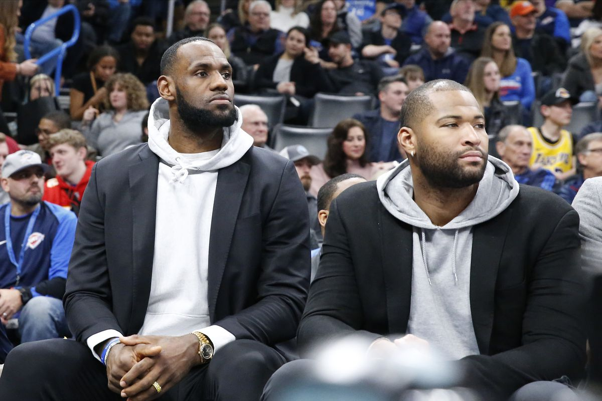 Los Angeles Lakers forward LeBron James and center DeMarcus Cousins watch play from the bench against the Oklahoma City Thunder during the first half at Chesapeake Energy Arena.