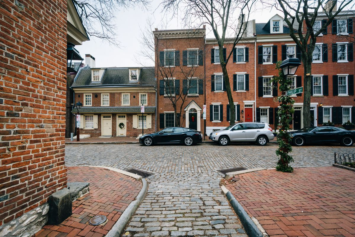 A series of brick rowhomes on a brick-paved street in Society Hill.