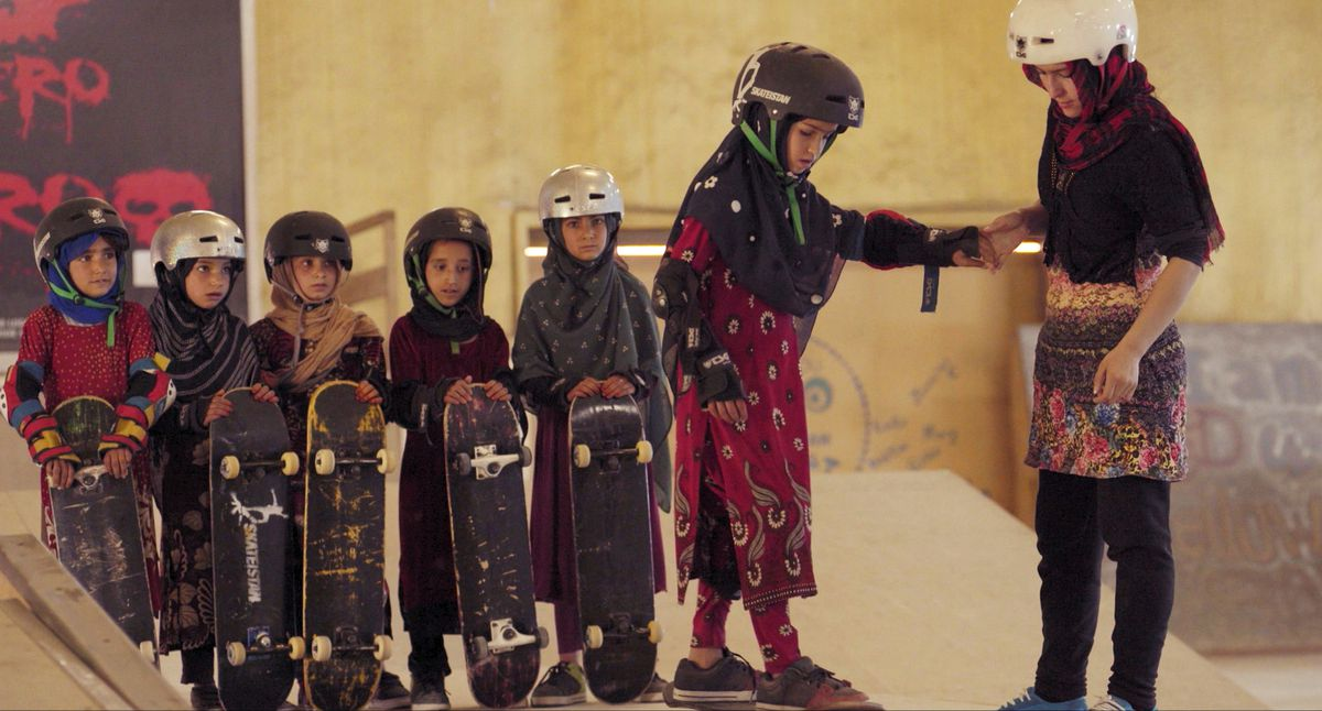 A young women teaches several girls to skateboard inside a school in Afghanistan in the documentary Learning to Skateboard in a Warzone (If you're a Girl)