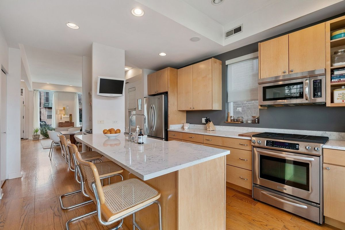 A kitchen with a large breakfast island that has four chairs, lots of cabinet space, and stainless steel appliances.
