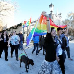 Nikki Jensen and Coco Barth carry a flag over their heads while marching around Temple Square after the LDS Church Mass Resignation at City Creek Park in Salt Lake City on Saturday, Nov. 14, 2015.