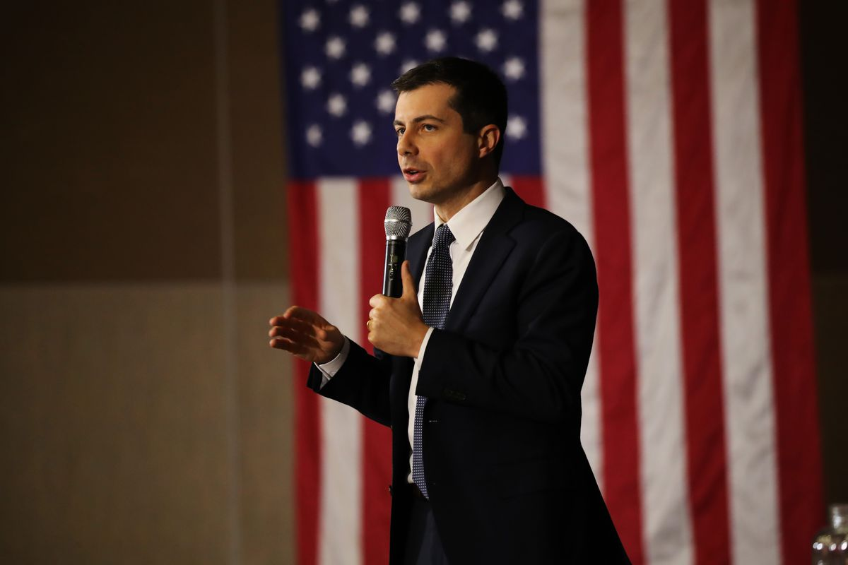 Pete Buttigieg speaks into a microphone in front of an American flag.
