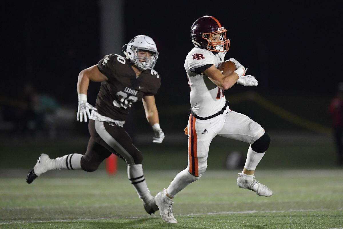 Brother Rice's Kevin Phelan runs with the football in front of Mount Carmel's Austin Maciel-Haygood.