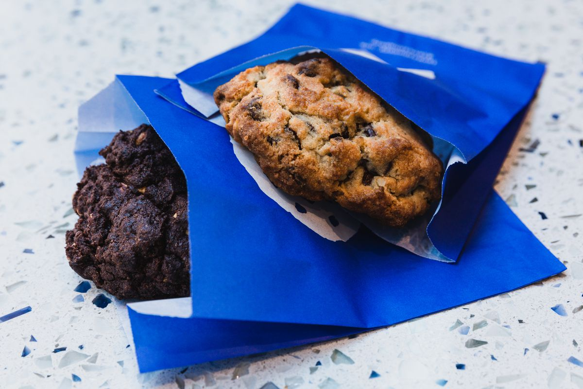 Two chocolate chip cookies — one dark, one golden brown — rest on top of one another in blue to-go sleeves