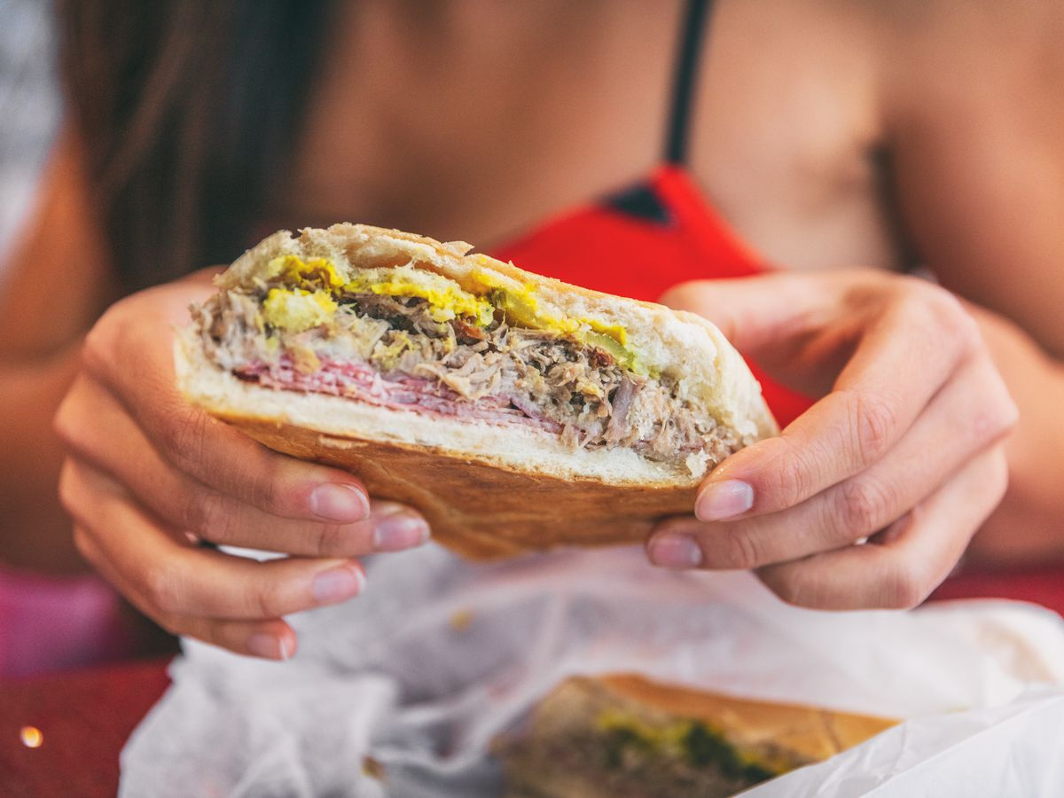 A woman holds up a cross-section of a cubano sandwich
