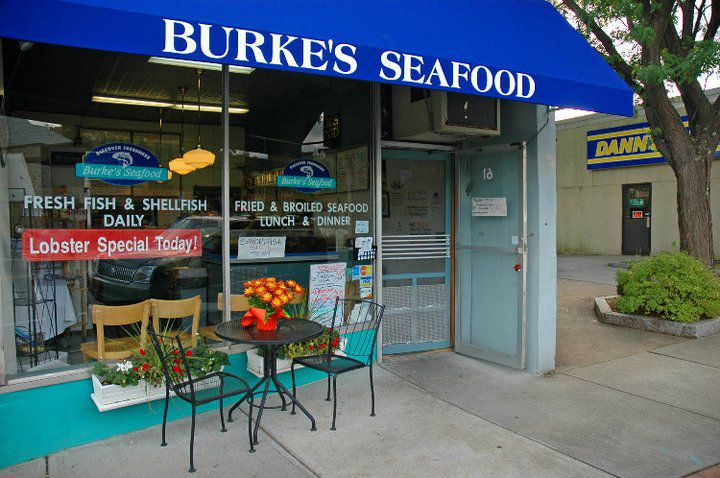 Exterior view of a small seafood shop with a royal blue awning. A small two-seat table sits outside the front window, on the sidewalk.