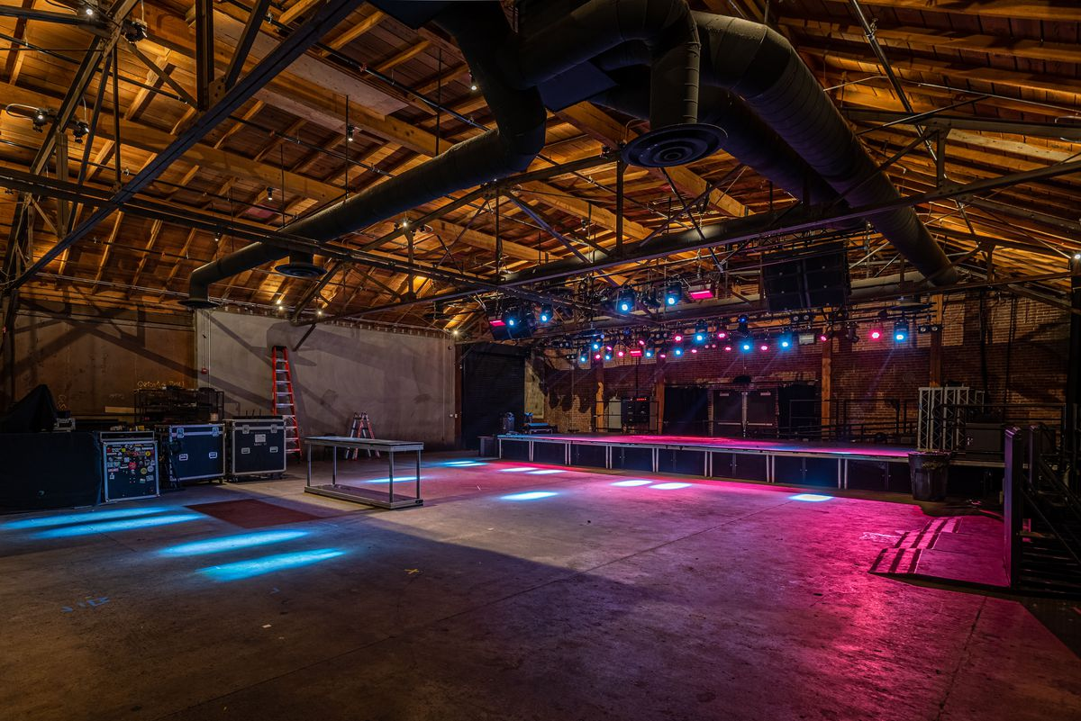 A deep, empty music venue with lights set on stage.
