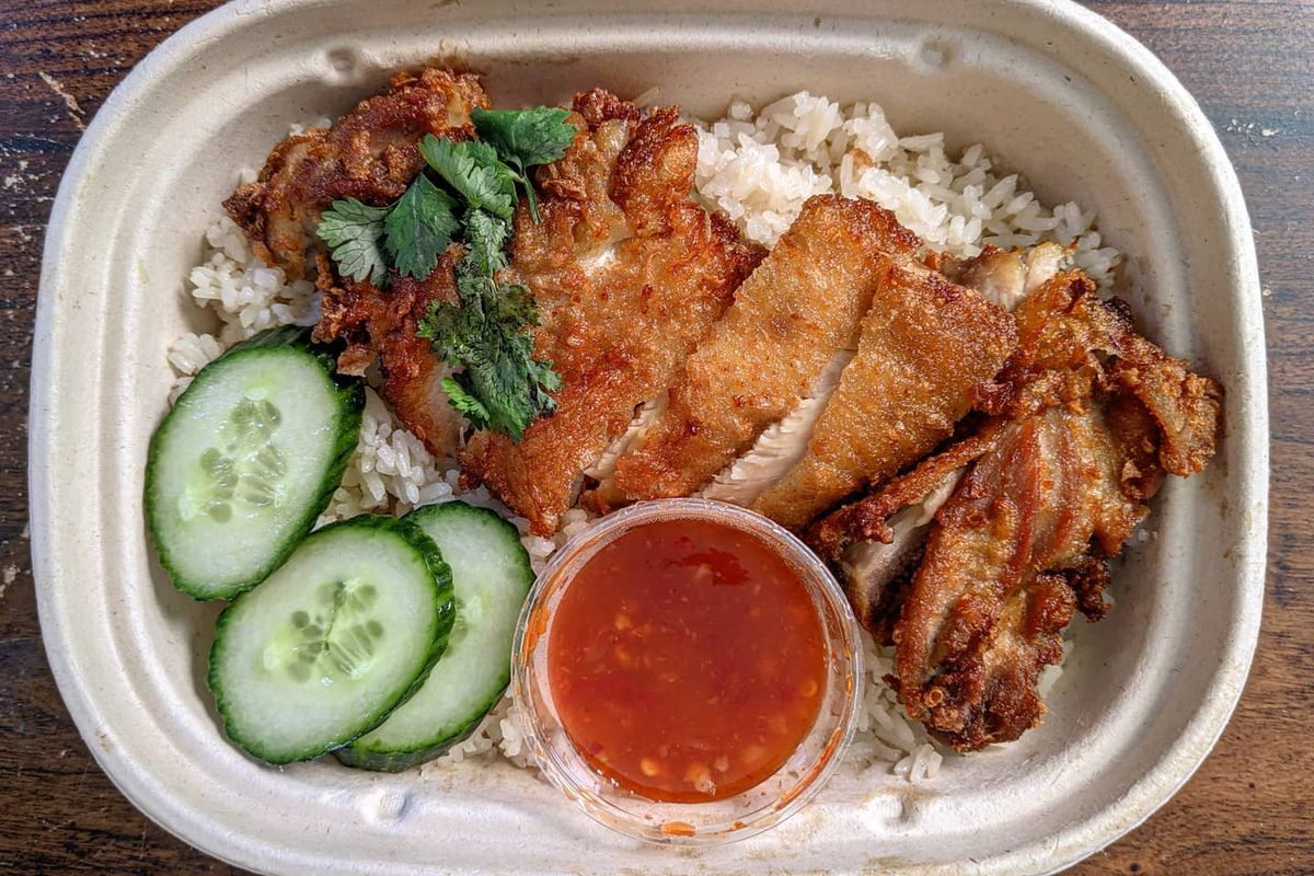 overhead view of a compostable takeout container of crispy chicken slices over rice, with cucumber and cilantro garnish and a plastic cup of a sweet chile sauce