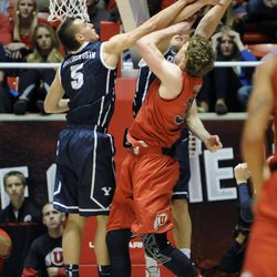 Utah Utes center Dallin Bachynski (31) is fouled by Brigham Young Cougars guard Tyler Haws (3) as Brigham Young Cougars guard Kyle Collinsworth (5) is also involved in the play during a game at the Jon M. Huntsman Center on Saturday, Dec. 14, 2013.