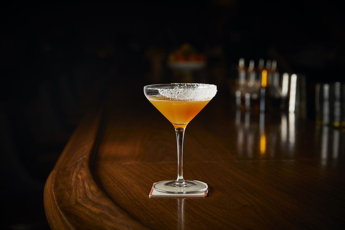 The photo shows a cocktail in a white glass placed on a wooden bar.