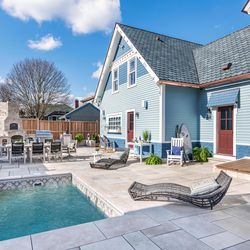 Cooking, eating, and cooling-off zones make up the outdoor living area. <em>Landscape contractor: </em><a class=