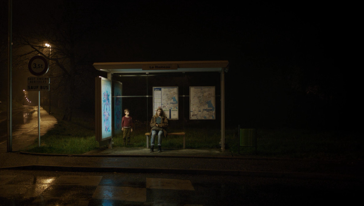 Child standing behind woman at bus stop.
