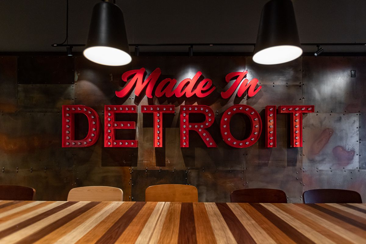 A red light up sign that reads Made in Detroit hangs on the wall next to a long striped wood table.