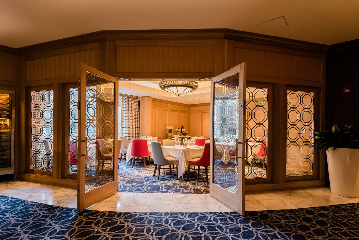 Double doors open into a carpeted dining area with white tablecloths and plush chairs