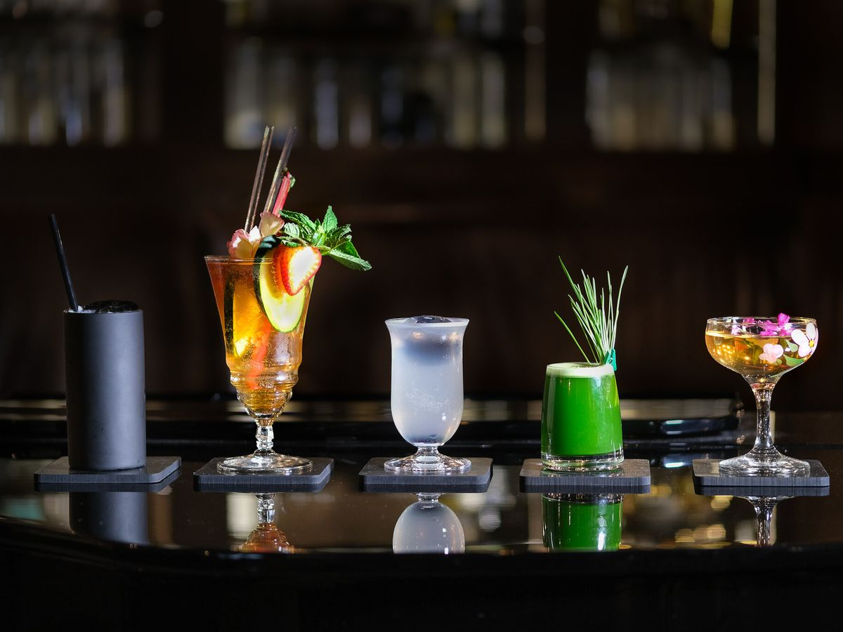 A selection of drinks on a black background including one black collins glass, one clear garnished with apples and cinnamon, one opaque like a clarified milk punch, one shockingly verdant green with a grassy garnish, and a coup glass with flower petals mixed into an amber liquid