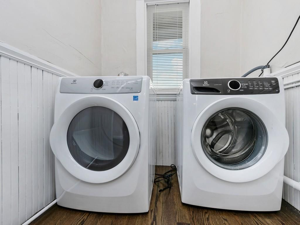 A washer and a dryer side by side in a narrow room.