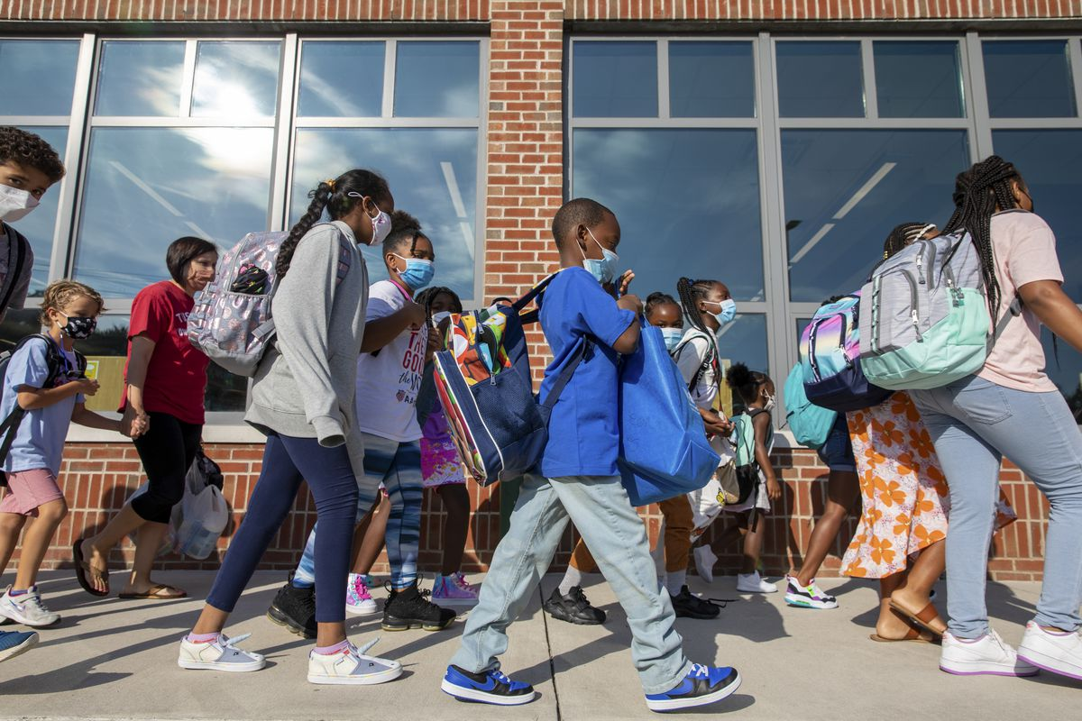 Elementary school students carrying backpacks and wearing masks walk along the sidewalk in front of their school on their way into the building.