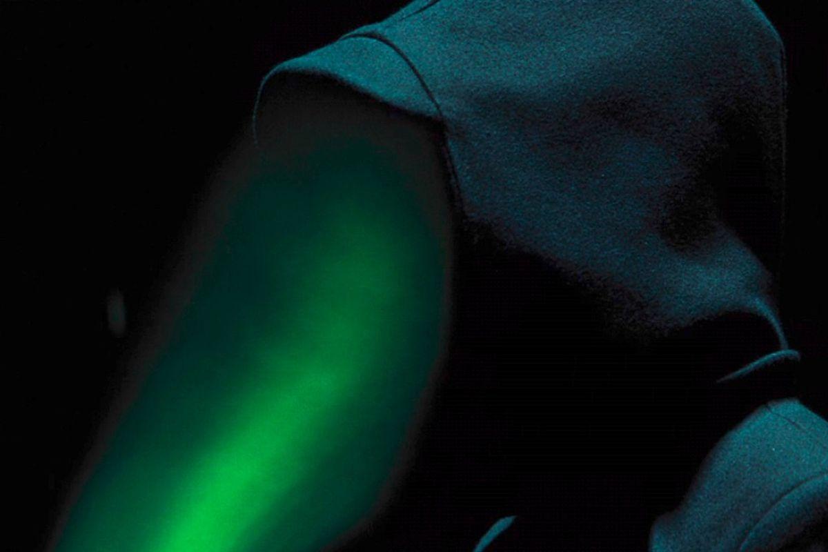 Hooded Artemis Fowl villain (Opal Koboi?) speaks into her green beam communication device
