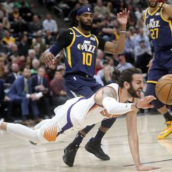 Phoenix Suns guard Ricky Rubio (11) reaches for the ball as he falls in front of Utah Jazz guard Mike Conley (10) and Utah Jazz center Rudy Gobert (27) during an NBA game at the Vivint Smart Home Arena in Salt Lake City on Monday, Feb. 24, 2020.