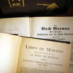 Historic title pages of the Book of Mormon in German and Spanish.    The cover of the Book of Mormon is written in Mandarin Chinese.
