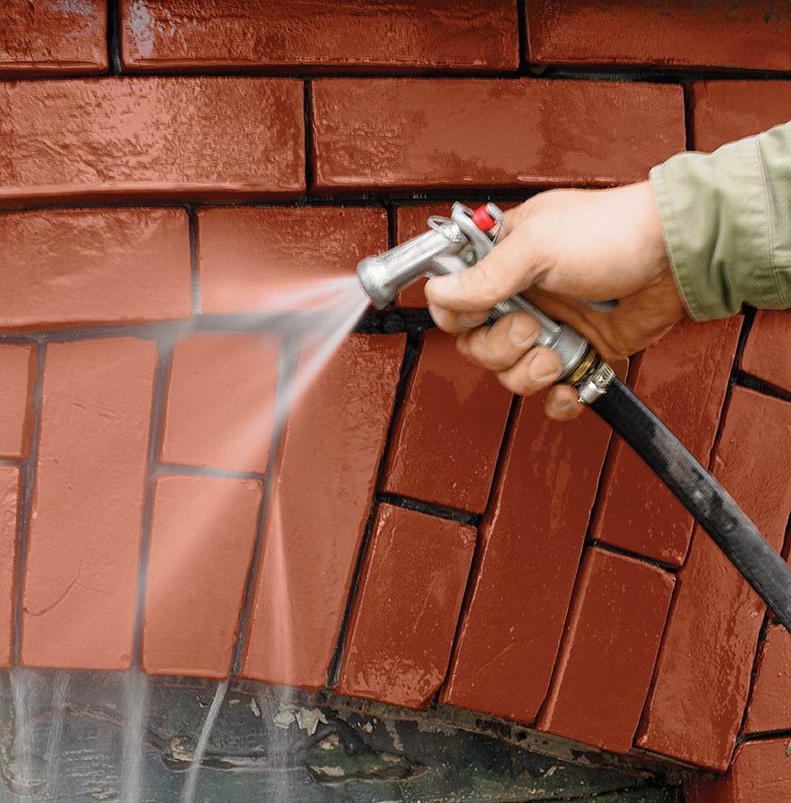 Person washing brick wall to prepare apply mortar.