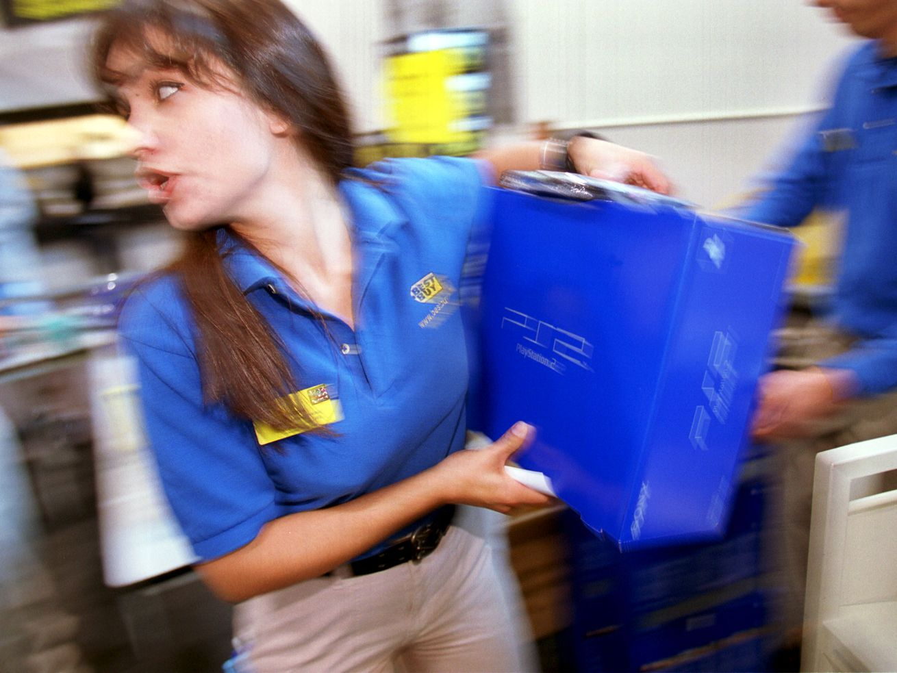 A saleswoman carries a boxed Sony Playstation through a Best Buy store.