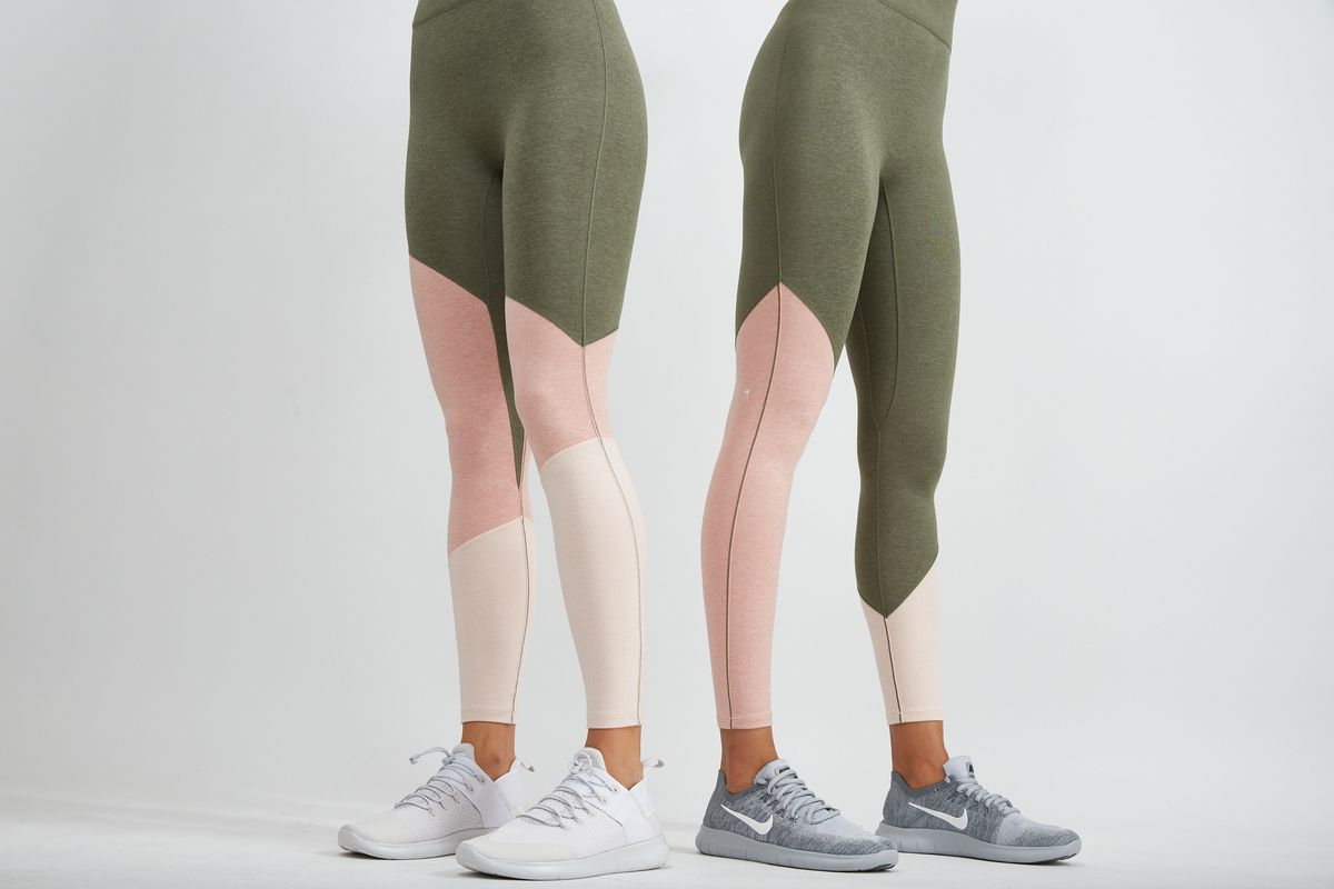 Two women wear color blocked olive, pink, and white leggings.