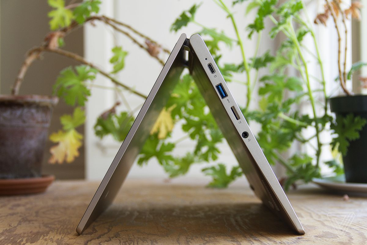 The Lenovo Ideapad Flex 3 in tent mode, seen from the left side, with two houseplants in the background.