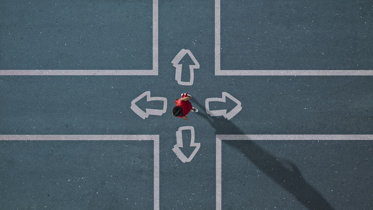 Arrows pointing in different directions on the street surround a child photographed from above.